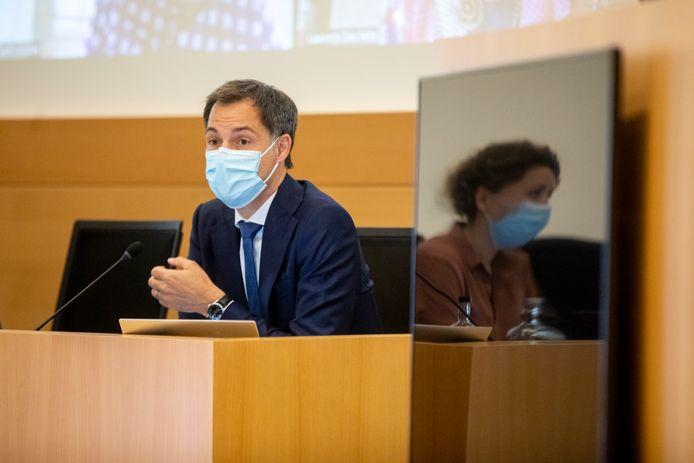 Premier Alexander De Croo (Open Vld) gisteren in het parlement. Rechts gespiegeld in een scherm is staatssecretaris Sarah Schlitz te zien.
