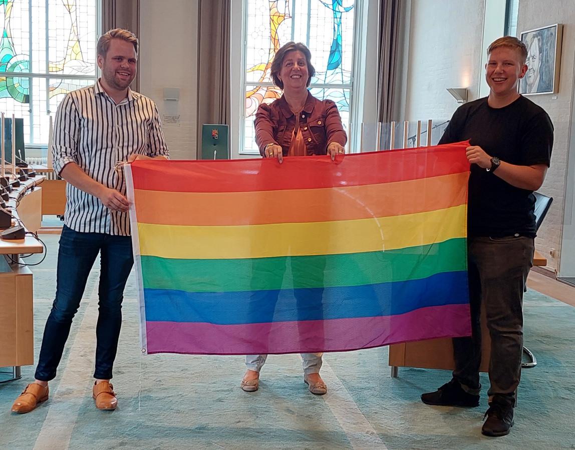 François (links) en Maxim (rechts), de kersverse regenboogambassadeurs van de gemeente Kapelle, houden samen met wethouder Annebeth Evertz de regenboogvlag omhoog.