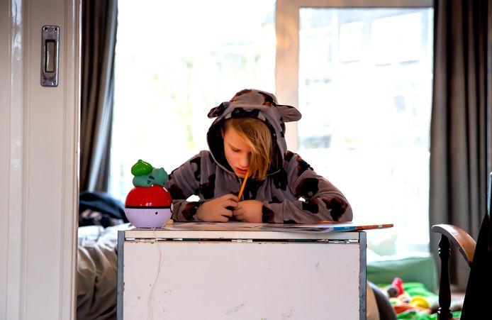 Boris (9) maakt thuis zijn schoolwerk.