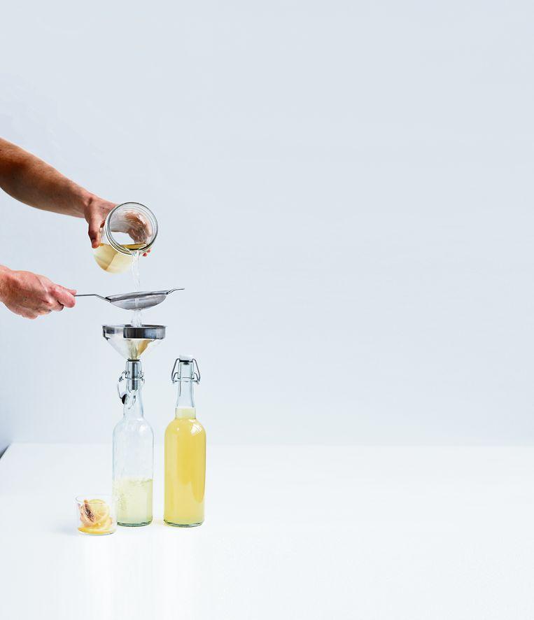 Kombucha in glazen flessen gieten. Beeld Uit het boek Kefir & Kombucha, Sebastian Landaeus