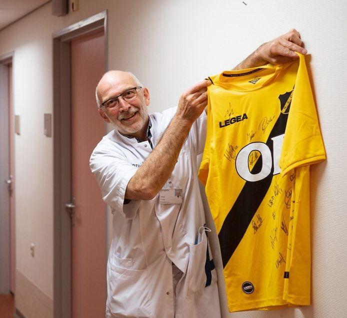 Een tevreden Peter Joosten toont het nieuwe shirt van NAC, woensdag afgeleverd door Mario Bilate.