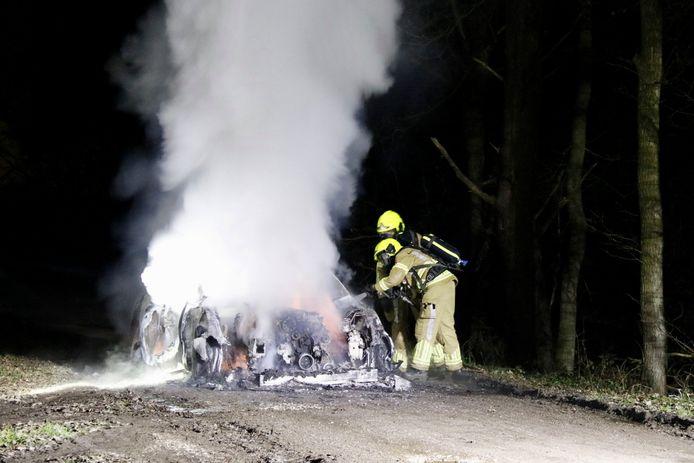 Brandweermannen blussen de personenwagen die vannacht uitbrandde op de Heiweg langs de Black in Heijen.