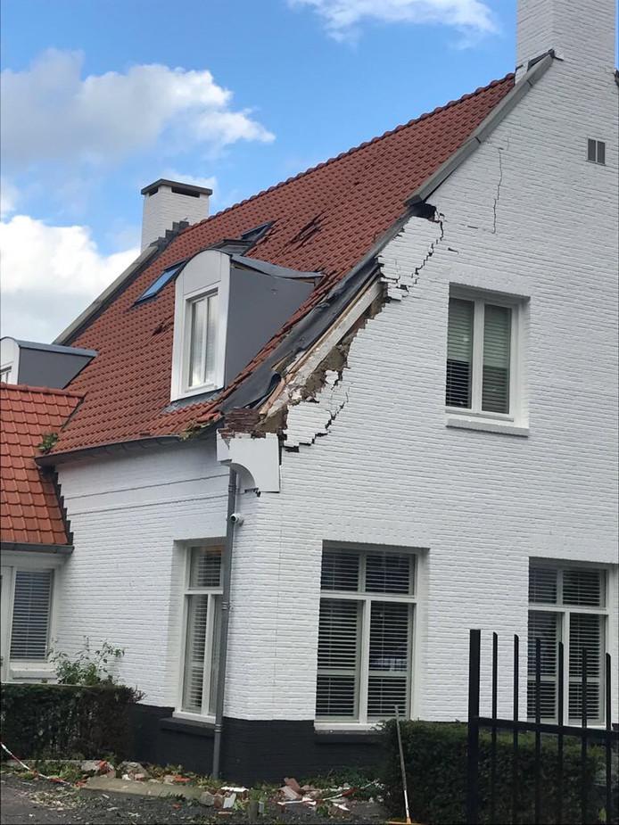 De gevel van de bewuste woning liep flinke schade op door de omgevallen boom.