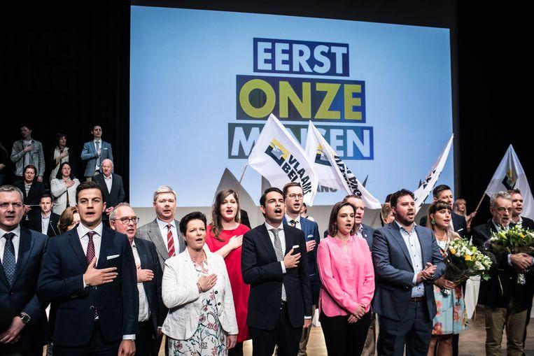 Tom Van Grieken (midden) en andere Vlaams Belangers zingen de Vlaamse Leeuw op hun verkiezingscongres van 30 maart. Beeld Bas Bogaerts