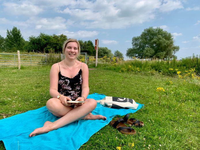 Celine Kuipers heeft zichzelf getrakteerd op een vrije middag langs de Waal en leest een boek.