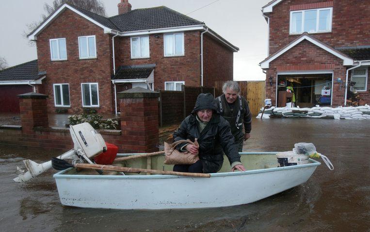 Inwoners van Moorland (Somerset) stappen in een boot. Beeld getty