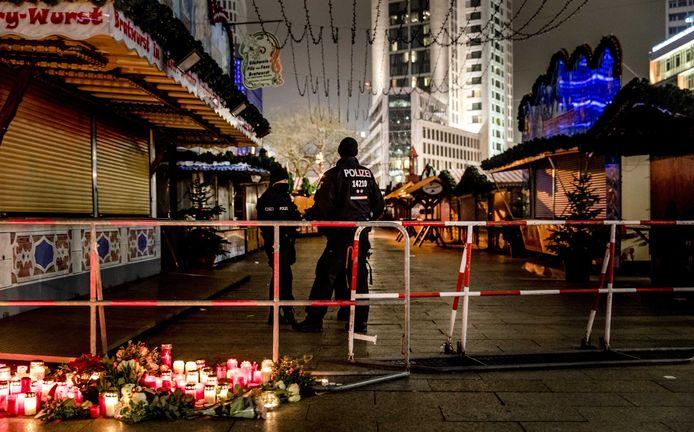 Kaarsen en bloemen bij de de plek van de aanslag. Op de achtergrond de Gedächtniskirche.