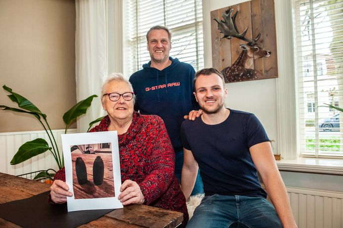 Ruim 30 jaar geleden kocht Jopie van Leeuwen 'gewichtjes' op de rommelmarkt. Het bleken granaten. Ze houdt een fotoprint vast van de granaten. Naast haar Niels van Egmond (27) en zijn vader Sjaak van Egmond.