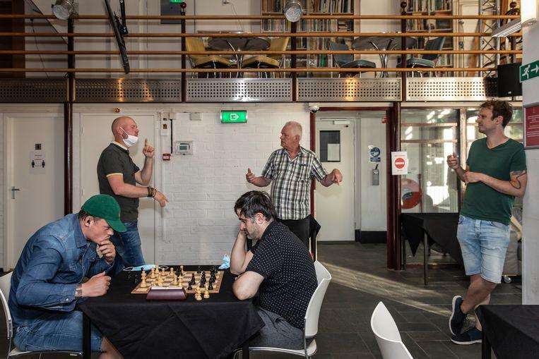 Saïd Jamal Alyass (rechts), aan het schaken. Achter hem staat Henk Havik (geruite blouse). Beeld Dingena Mol