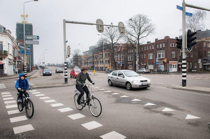 Fietsers op de Graafseweg, waar één rijstrook staduitwaarts aan de overzijde bij de brug plaatsmaakt voor een fietspad.