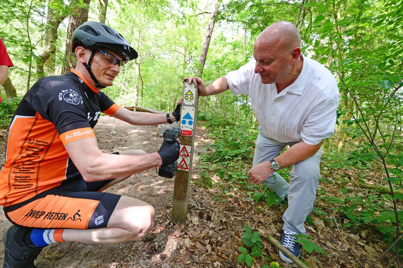 De Mountainbikeroute Het Hulsbeek heeft als eerste in Nederland de nieuwe borden gekregen, die sporters vertellen hoe zwaar en gevaarlijk het parcours is. Wethouder Benno Branden Peter Wolters van het Twentse Ros bevestigen de signaleringen.