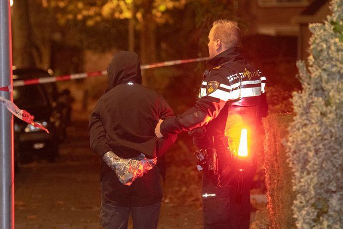 Eén van de verdachten die kort na de plofkraak in Nieuwkoop is aangehouden wordt naar een politiewagen gebracht.