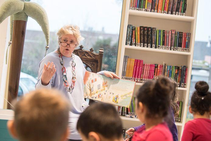 Vrijwilliger Annet den Braven leest voor in de bibliotheek.