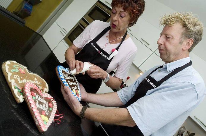 Karin en Frans van Morkhoven bespuiten kermiskoeken met suiker.