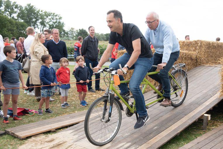Minister Alexander De Croo en de Oudenaardse burgemeester Marnic De Meulemeester op de tandem.