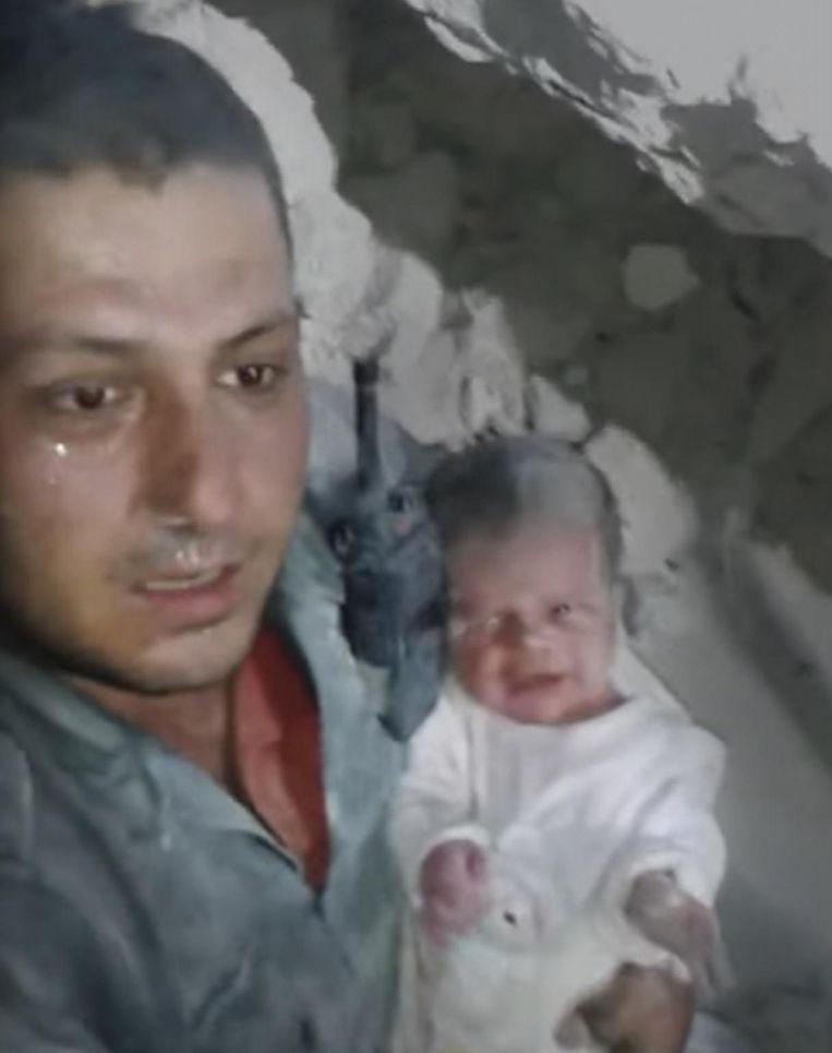 Khaled Omar Harrah in 2014 na de reddingsactie van een baby die onder het puin lag in Aleppo. Beeld Screenshot Youtube