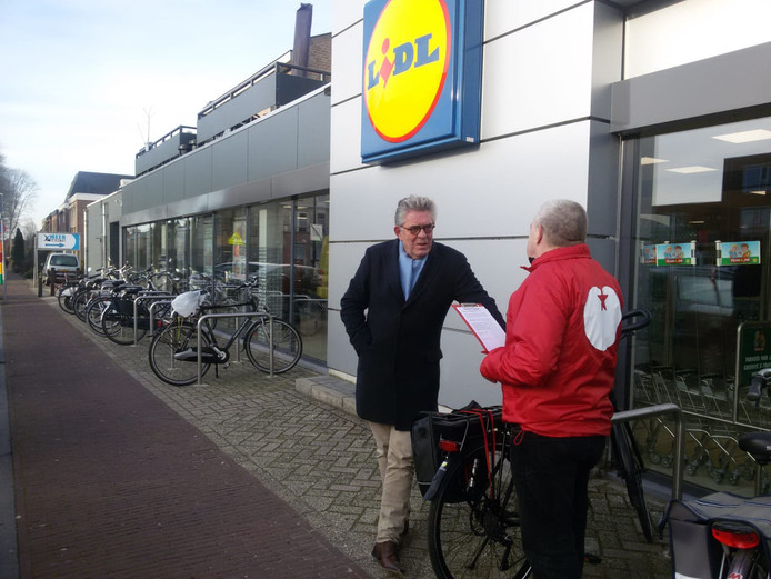 Fractievoorzitter Jan Raaimakers (rechts) legt een bezoeker van de Lidl vragen voor over het nieuwe gezondheidscentrum aan de Cereslaan.