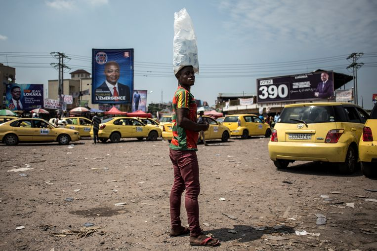 Een man verkoopt water op een parkeerterrein voor taxi's in de wijk Lingwala in Kinshasa. Rondom hangen overal verkiezingsaffiches.  Beeld AFP