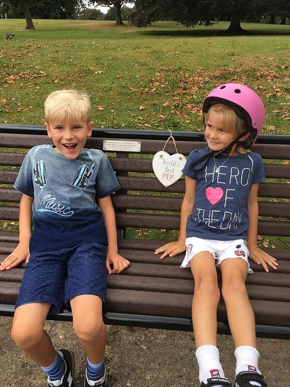 De kinderen van Daniel en Nikki op een gedenkbank voor hun mama.