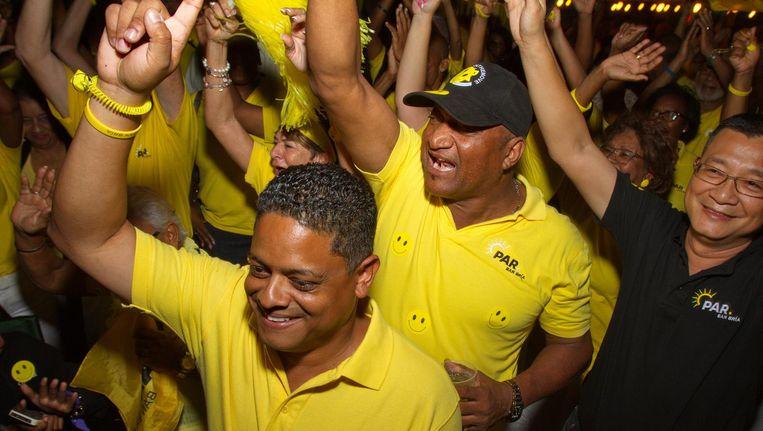 PAR-lijsttrekker Eugene Rhuggenaath (L) viert met zijn aanhang de overwinning van de verkiezingen op Curacao. De partij PAR is de grote winnaar met 6 zetels in een parlement met 21 leden. Beeld anp
