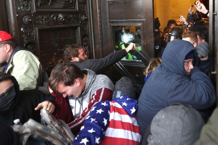 Trump-aanhangers dringen het gebouw binnen. Beeld Getty Images