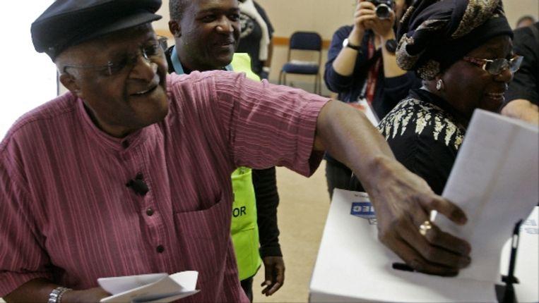 Bisschop Desmond Tutu doet zijn stembriefje in een stembus in Kaapstad. (AP) Beeld AP