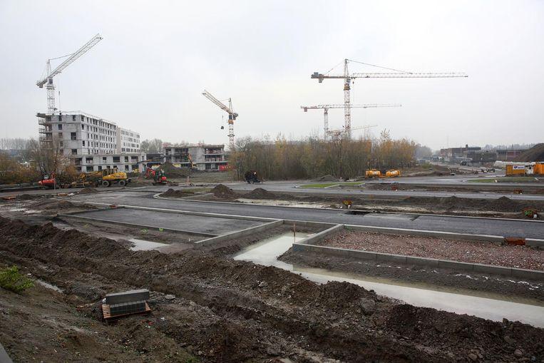 Op deze site werd asbestvervuiling vastgesteld tijdens wegenwerken. Op de achtergrond is de bouw van nieuwe appartementen en huizen volop bezig.