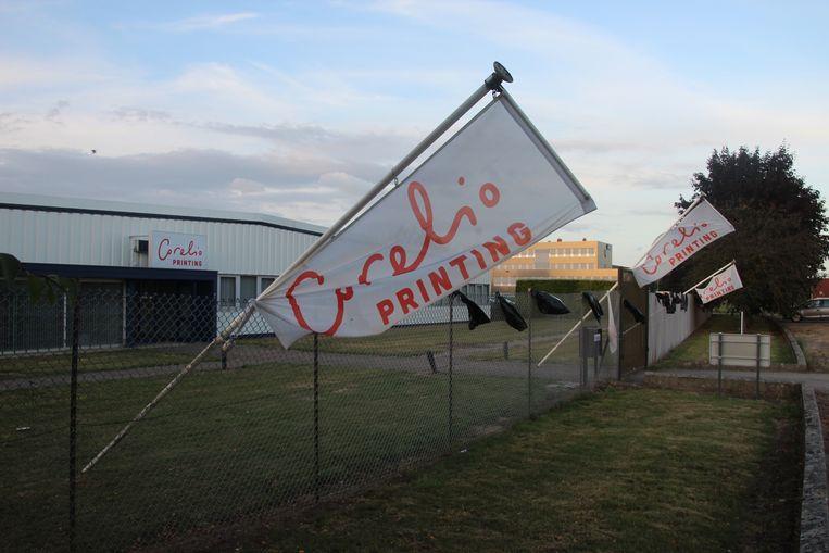 Aan de buitenhekken van Corelio Printing werden zwarte vlaggen opgehangen.