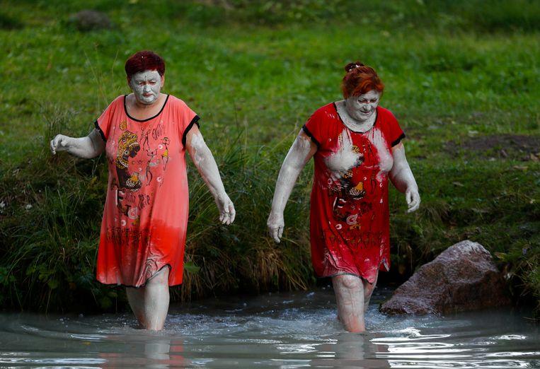 Tijdens de jaarlijkse viering in de Russisch-orthodoxe kerk waarbij de zegeningen van honing en water een rol spelen, nemen twee vrouwen in Wit-Rusland een ritueel bad in de omgeving van Slavgorod. Beeld REUTERS