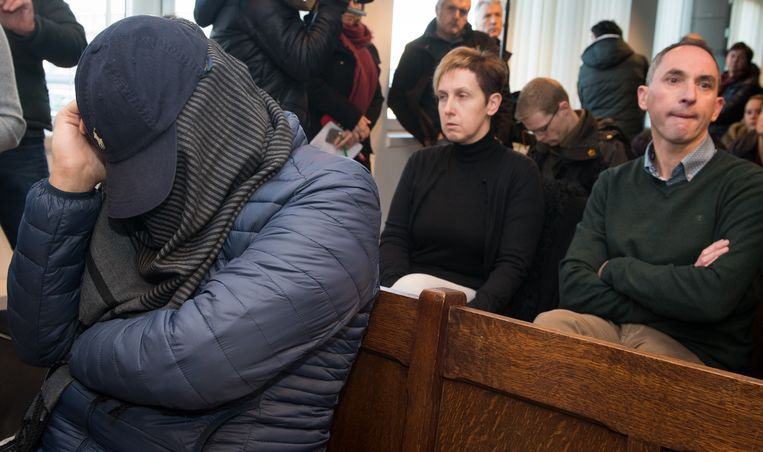 De doodrijder van de 12-jarige Merel De Prins bedekt zijn gezicht tijdens de start van zijn proces. Achter hem zitten de ouders van het verongelukte meisje. Beeld BELGA