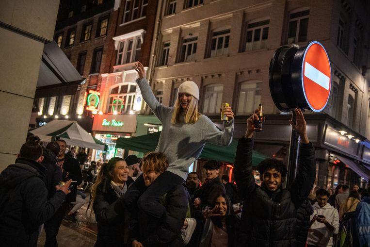 Jongelui drinken in de Londense wijk Soho. In het VK opent de horeca opnieuw zijn deuren.  Beeld Getty Images