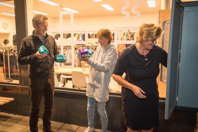 Jeroen Dijsselbloem helpt Petra van Amersfoort (links) en Jolanda Fennema om het menstruatiekastje te vullen. Even daarvoor heeft de oud-minister het eigenhandig aan de muur bevestigd naast de Ontmoetingswinkel van het Leger des Heils in Wageningen.
