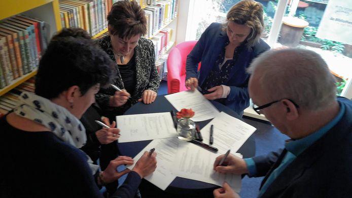 Vertegenwoordigers van diverse partijen, waaronder wethouder Jan Bevers van de gemeente Gemert-Bakel (rechtsonder) ondertekenen het Taalhuis-convenant.