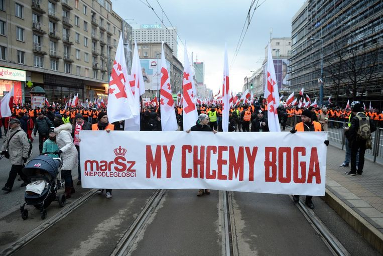 Demonstranten dragen een spandoek met de tekst 'Wij willen God' door Warschau. Beeld epa