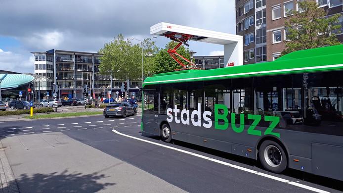 Een bus van Qbuzz laadt op aan de snellader bij een winkelcentrum in Dordrecht.