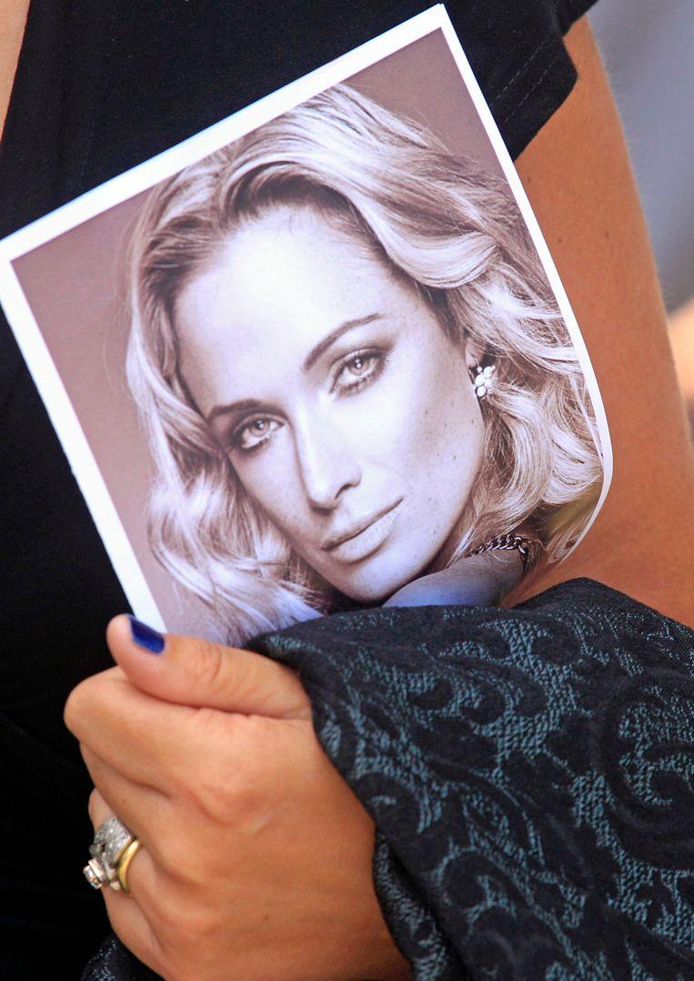 Tijdens de begrafenis van Reeva Steenkamp in februari 2013 houdt een van de rouwenden een foto van haar vast. Beeld AP