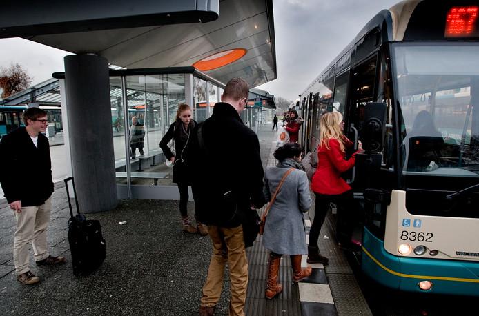 Mensen stappen in de bus op busstation Heinenoord