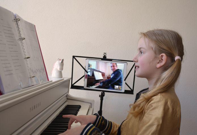 De 9-jarige Kirsten krijgt online pianoles van haar CKB docent Erwin Leijs.