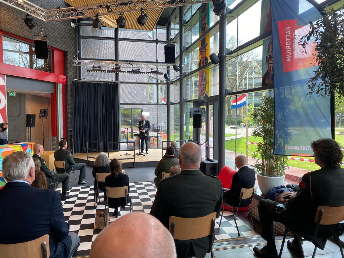 Weterings spreekt zijn speech uit in het Factoriumgebouw naast het Vrijheidspark, waar de vlag halfstok hangt.