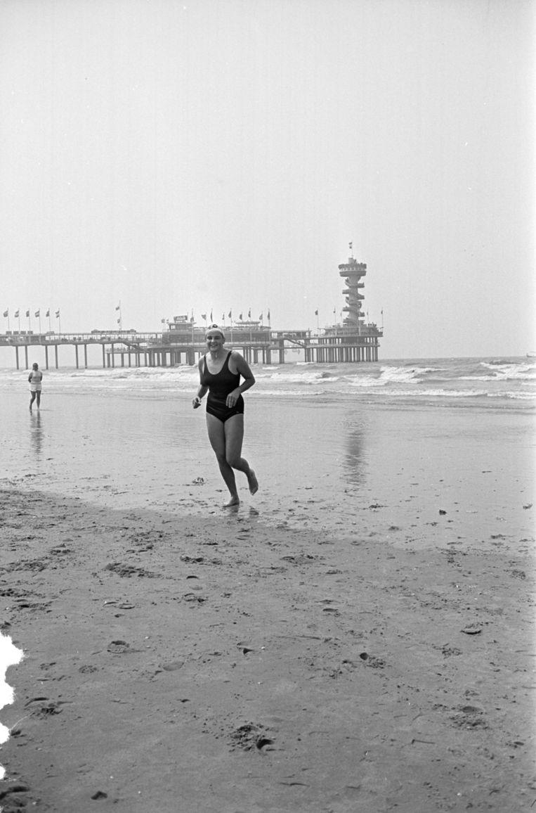 Erica Terpstra komt als eerste aan het land tijdens een zwemwedstrijd, juli 1963. Beeld anp