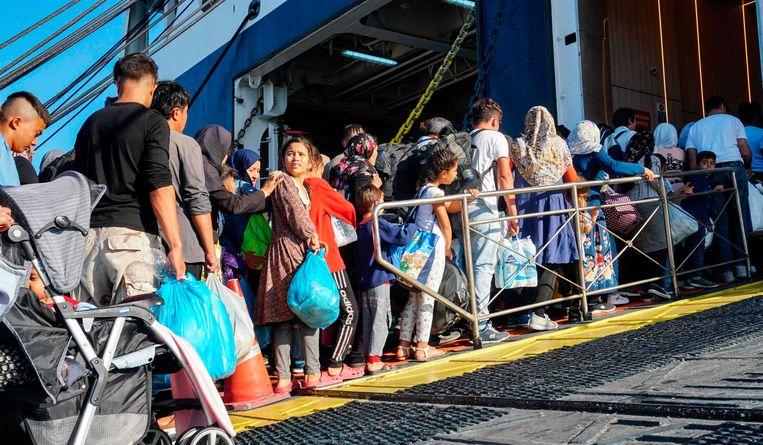 Vluchtelingen gaan aan boord van een ferry ops Lesbos. Beeld AFP