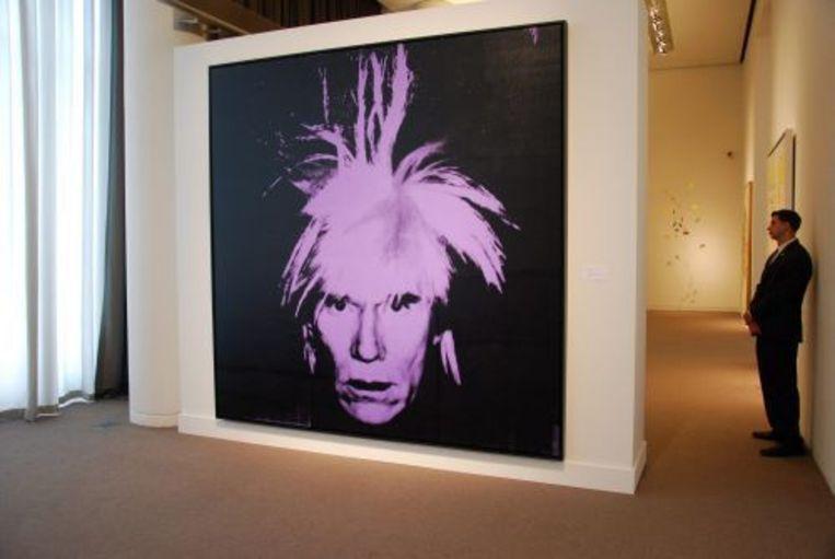 Het zelfportret van Andy Warhol wordt bewaakt door een beveiligingsbeamte. ANP Beeld