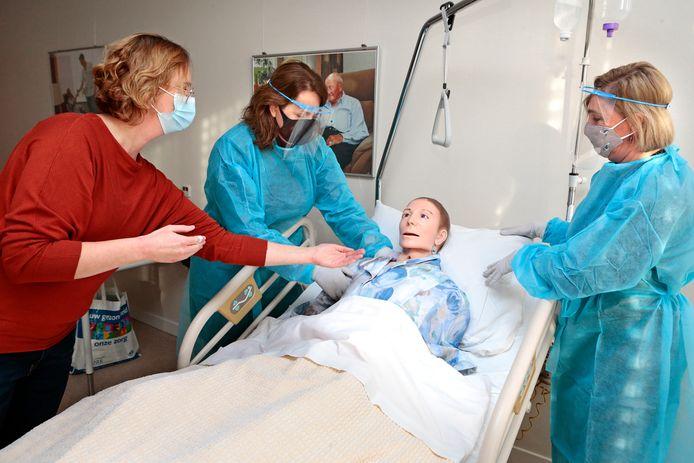Marcella van Steenis (links) geeft uitleg over de verzorging van een 'patiënt' aan Anja Evertse en Sonja Welten (rechts).