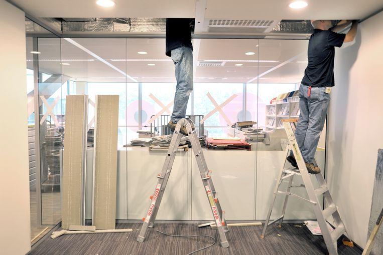 Installateurs aan het werk aan een ventilatiesysteem in een plafond. Beeld Joost van den Broek / de Volkskrant