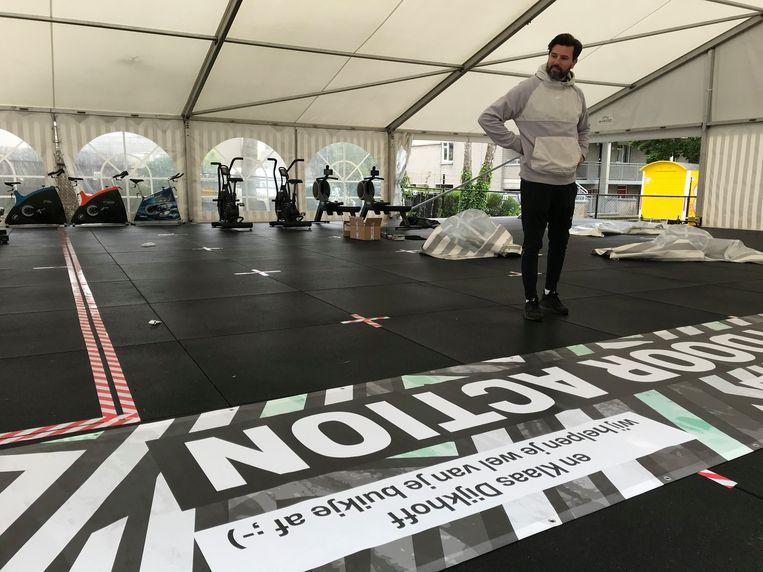 Sportschool Indoor Action in Arnhem heeft op een aangrenzend eigen parkeerterrein een festivaltent geplaatst om de leden buiten te kunnen laten sporten. Clubmanager Michel de Boer bekijkt de vorderingen van de bouw van de tent. Beeld Gert Jan Rohmensen
