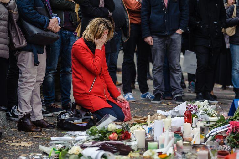 Mensen leggen bloemen vlakbij de concertzaal Bataclan in de week na de aanslag daar. Beeld EPA