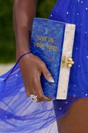De clutch van Amanda Gorman in de vorm van een boek met opschrift 'Give us your tired', een verwijzing naar het gedicht dat op het Vrijheidsbeeld te lezen staat.