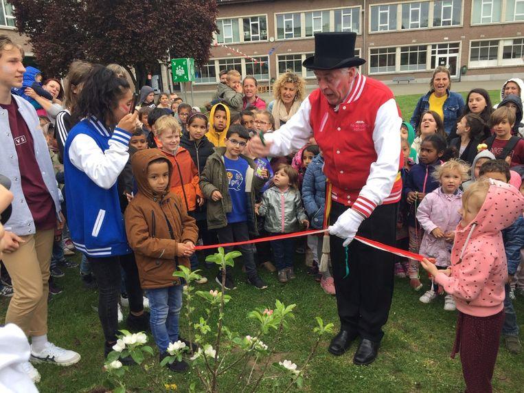 Burgemeester Samson knipt lint door waarna hij een boompje op de speelplaats van Atheneum Tungrorum plant.