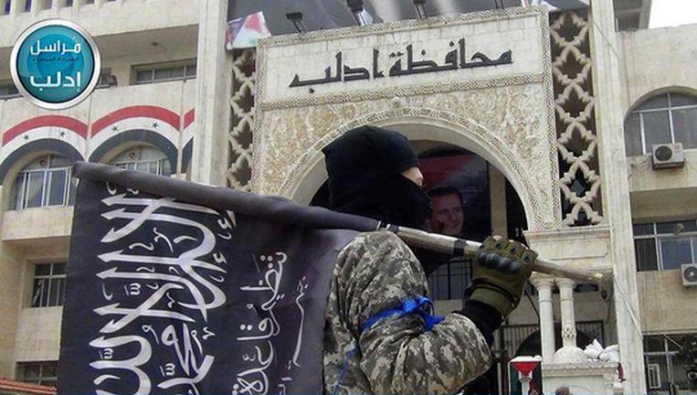 Een Al Nusra-strijder met zijn vlag in Idlib, Syrië. Beeld AP