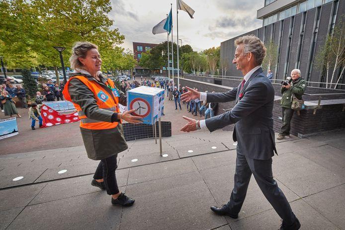 Tegenstanders van de windmolens overhandigen een petitie aan wethouder Johan van der Schoot.